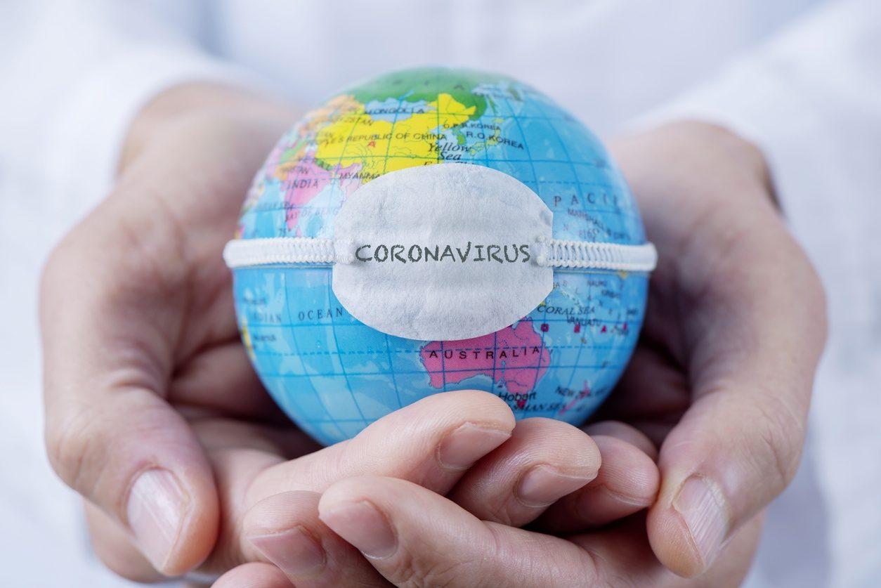 Deux mains portent un globe terrestre porte un masque avec inscrit 'Coronavirus'