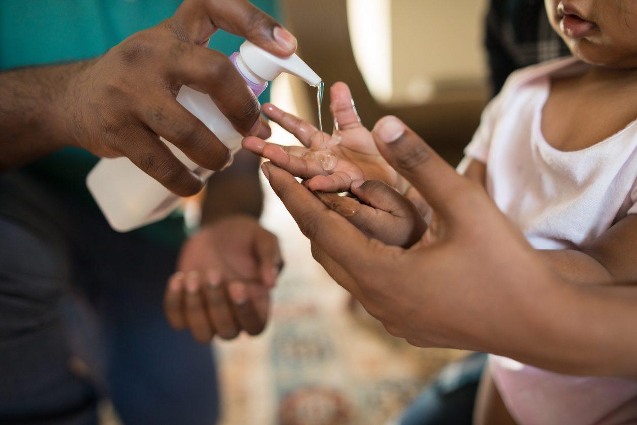 Parent apprenant à son enfant à se laver les mains avec du gel hydroalcoolique