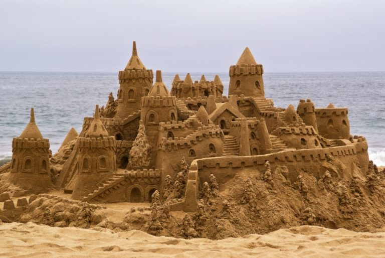 Chateau de sable sur la plage avec avec l'océan en arrière-plan.