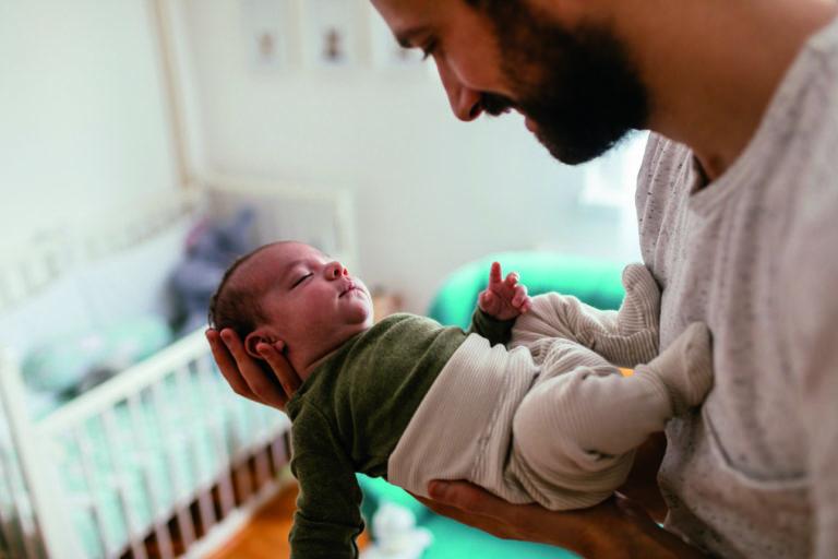 Un père tient son fils nouveau né dans les bras