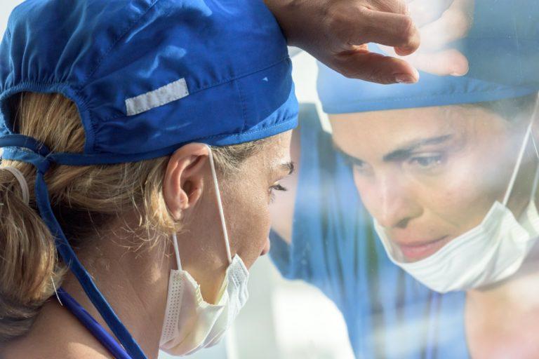 Femme médecin l'air grave regardant à travers une fenêtre