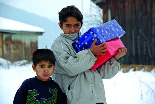 Deux enfants, dehors dans la neige recevant des paquets de Noël