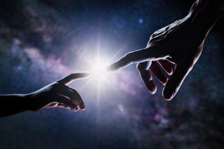 Gros plan de deux mains, adulte et enfant, se rejoignant comme dans la peinture de Michel-Ange devant les étoiles et la galaxie. La lumière brille entre les doigts du père et du fils.