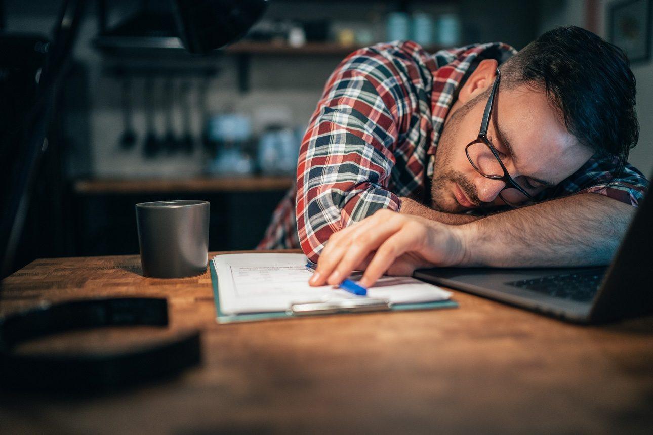 Un homme assoupi sur son bureau, devant son ordinateur
