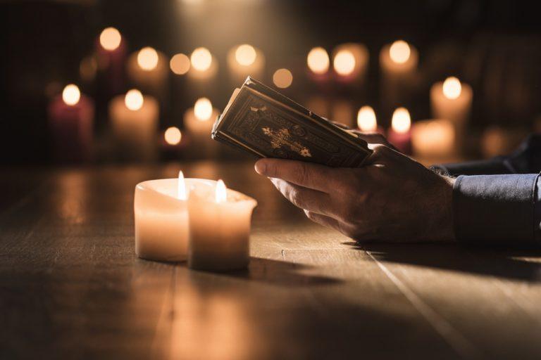 Un homme lisant sa Bible à la lumière de bougies