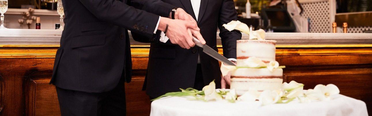 Couple homosexuel coupant le gâteau de mariage