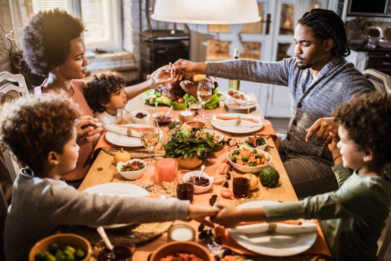 Famille afro-américaine se tenant la main et priant avant leur repas de Thanksgiving à la maison.