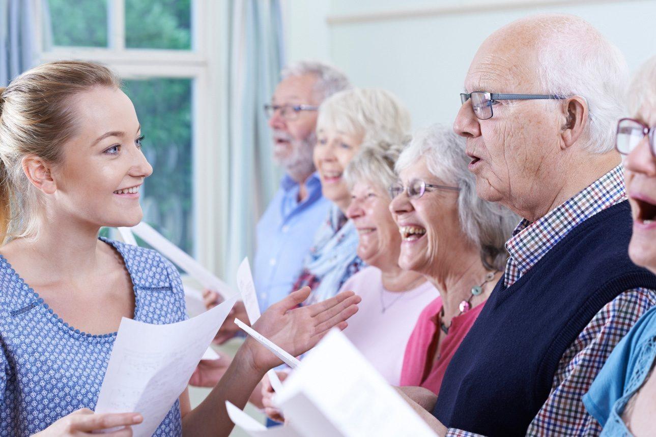 Groupe d'aînés avec professeur chantant en choeur ensemble
