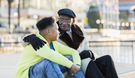 Un garçon afro-américain de 10 ans assis avec son arrière-grand-père de 79 ans, traînant sur un front de mer de la ville, en automne ou en hiver. Le vieillard a son bras autour de l'épaule de son arrière-petit-fils, lui donnant des conseils. Ils ont des expressions sérieuses sur leurs visages.