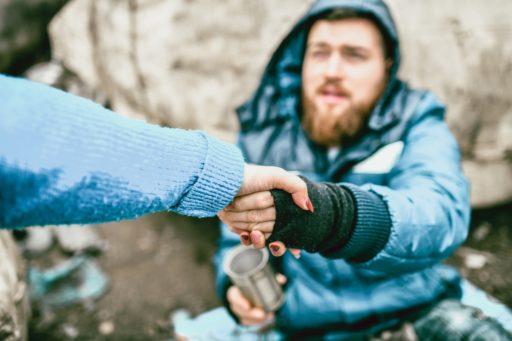 Une femme tend la main à un sans abri dans la rue