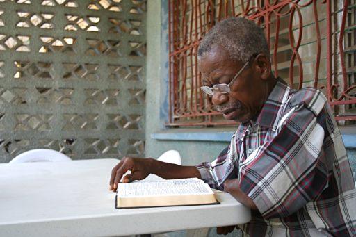 Un homme lisant sa Bible depuis sa terrasse