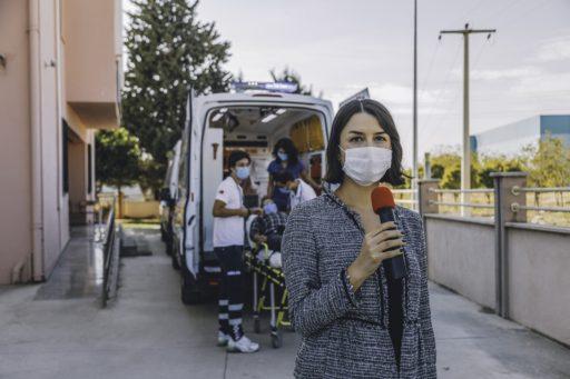 Une journaliste portant un masque rapporte les dernières nouvelles devant un hôpital pendant une pandémie