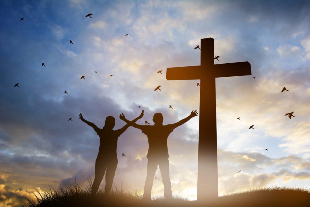 Une famille célébrant Dieu au pied d'une croix