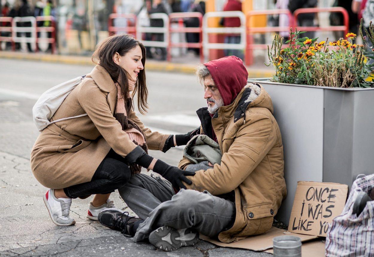 Une jeune femme prêtant attention à un homme sans abris, assis dans la rue