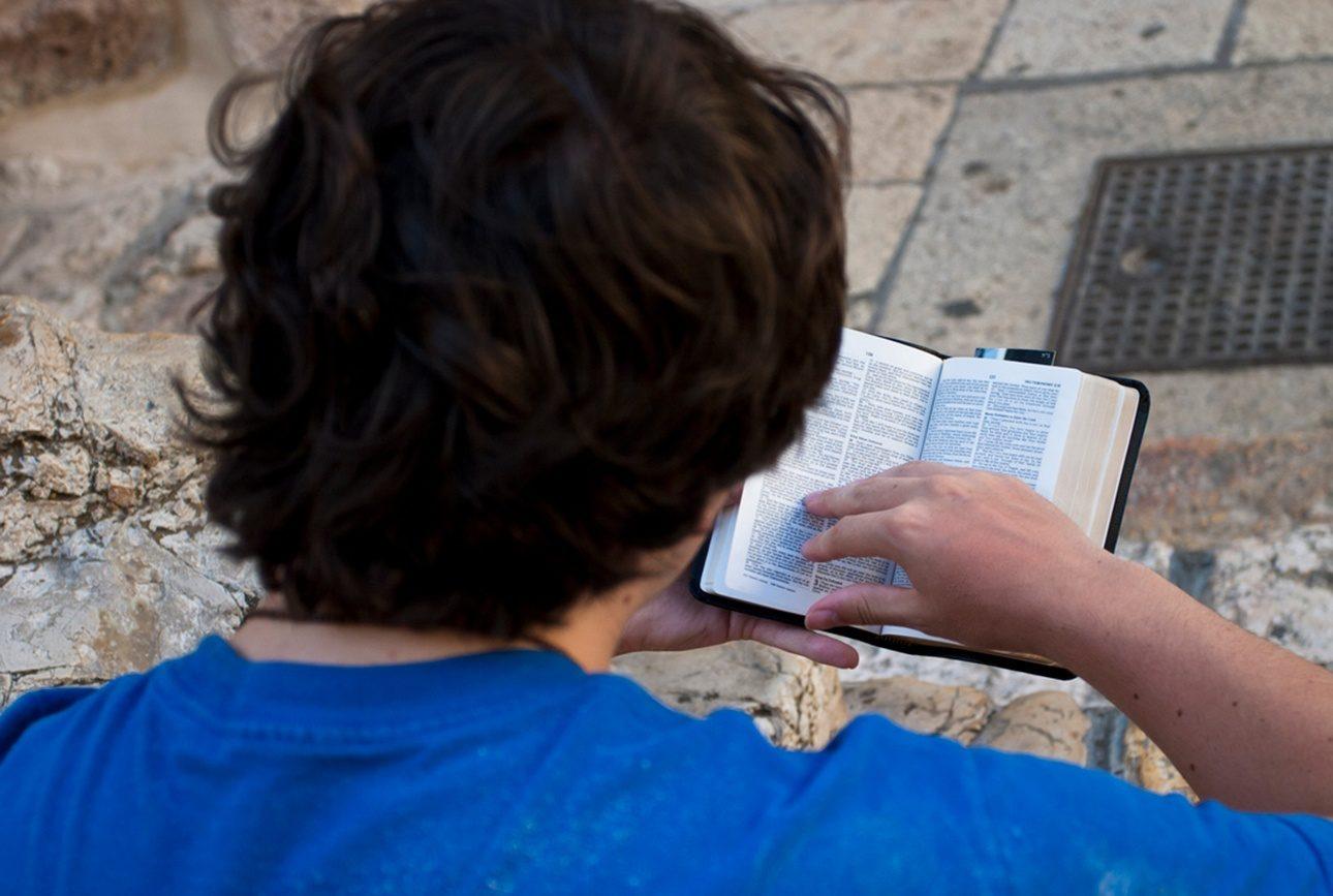 Jérusalem, Israël - 11 août 2006: pèlerin lisant le livre du Deutéronome devant l'église du Saint-Sépulcre