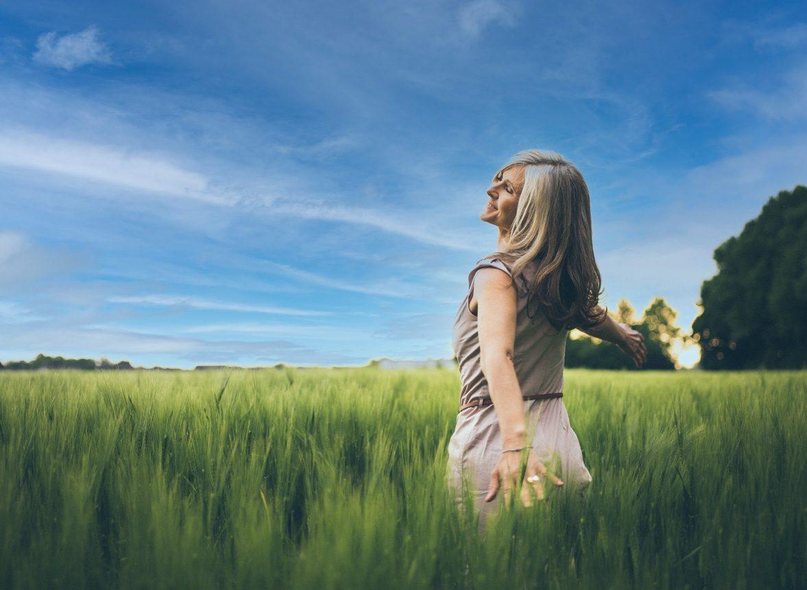Une femme dansant dans un champ de verdure, les cheveux au vent