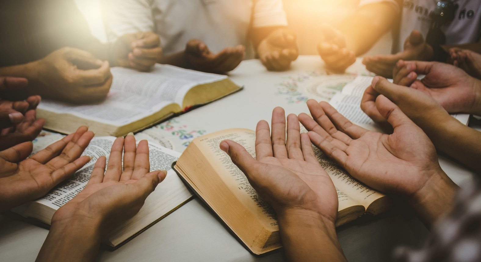 Un groupe de chrétiens priant et lisant la Bible ensemble, assis en cercle