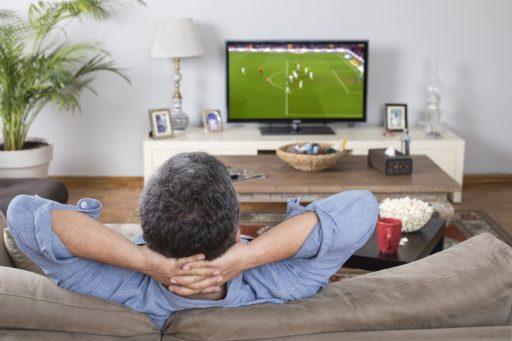 Un homme regardant un match de football à la télévision, bien installé dans son canapé.