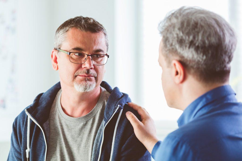 Image d'illustration présentant un homme apportant un soutien psychologique à un autre homme