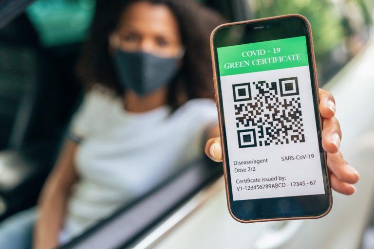 Une femme qui porte un masque anti-covid montre son certificat de vaccination sur son smartphone
