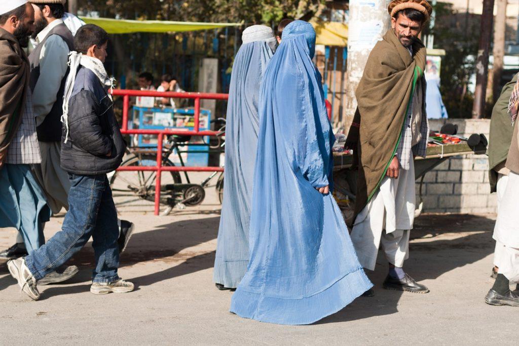 Un homme afghan avec ses deux femmes dans les rues de Fayzabad, Afghanistan