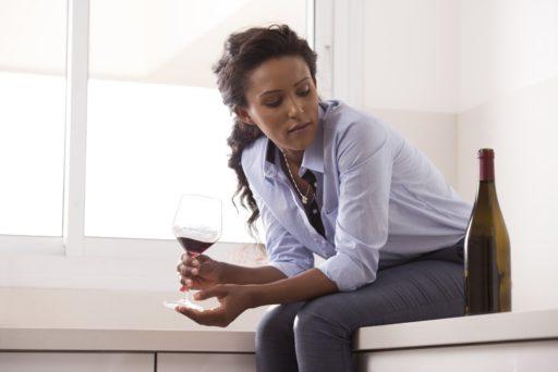 Femme d'affaires pensive assise sur le comptoir de la cuisine en marbre, tenant un verre de vin et regardant une bouteille de vin. Femme buvant de l'alcool, essayant de soulager le stress au travail.