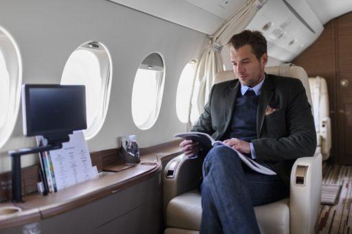 Un homme assis à l'intérieur d'un avion privé et lisant un magazine pendant le vol.