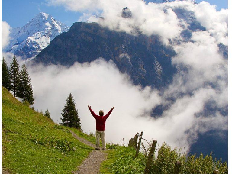 Un homme loue Dieu les bras levés dans les Alpes suisses