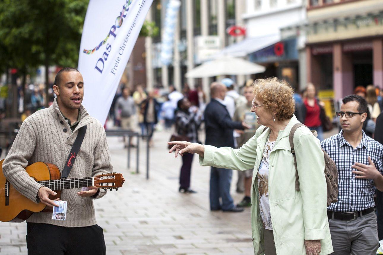 Wiesbaden, Allemagne - 16 juin 2012 : missionnaire chrétien. Un membre de la communauté chrétienne Pottershaus chante et prêche dans le centre-ville de Wiesbaden, en Allemagne, tandis qu'une femme âgée essaie de discuter avec lui