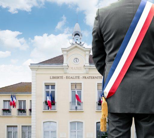 Un maire avec son écharpe tricolore devant sa mairie
