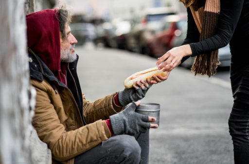 Une femme donnant de la nourriture à un mendiant sans-abri assis dans la rue.
