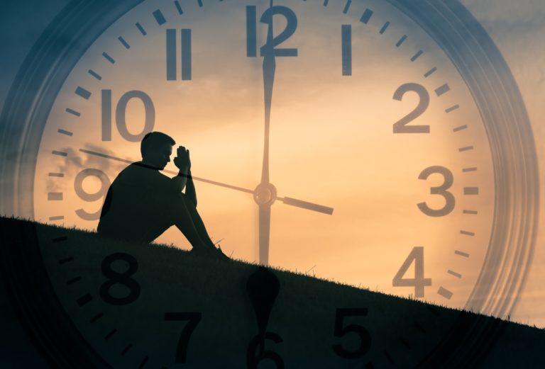 Double exposition d'un jeune homme priant à l'extérieur avec une horloge en arrière-plan.