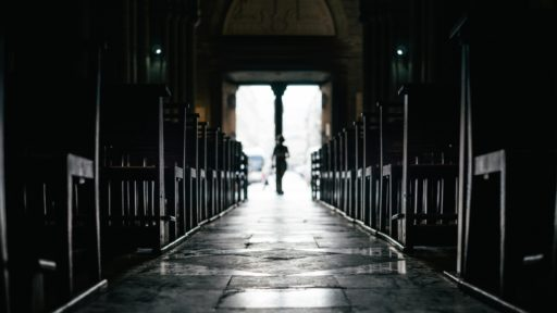 Des rangées de bancs à l'intérieur d'une église silencieuse avec des passants venant de la sortie